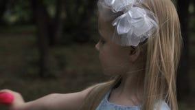 La petite fille souffle des bulles de savon en parc clips vidéos