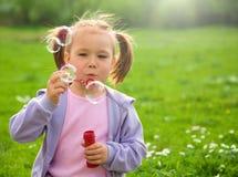 La petite fille souffle des bulles de savon sur le pré Photo stock