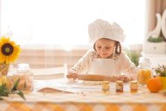 La petite fille sous forme de cuisinier déroule la pâte Photographie stock libre de droits
