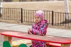 La petite fille sur le terrain de jeu Photo libre de droits