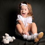 La petite fille sur un fond foncé rit Image stock