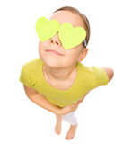 La petite fille tient des coeurs au-dessus de ses yeux Images stock