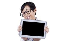 La petite fille tient le comprimé avec l'écran noir Photographie stock