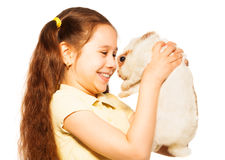 La petite fille tient le portrait étroit de lapin sur le blanc Image libre de droits