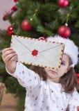 La petite fille tient Santa Letter Envelope Photographie stock libre de droits