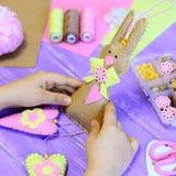 La petite fille tient un jouet de lapin de Pâques de feutre dans des mains La fille montre un lapin de feutre avec des coeurs Cad photographie stock libre de droits