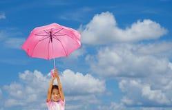 La petite fille tient un parapluie sur le ciel bleu images stock