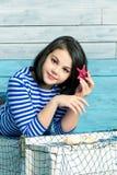 La petite fille tient une étoile de mer dans les cheveux Image libre de droits