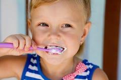 La petite fille tient une brosse à dents images libres de droits