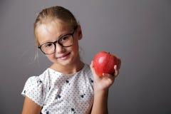 La petite fille tient une pomme Images stock