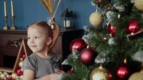 La petite fille très belle se tient près de l'arbre de nouvelle année et des jouets de contacts clips vidéos