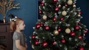 La petite fille très belle se tient près de l'arbre de nouvelle année et des jouets de contacts banque de vidéos