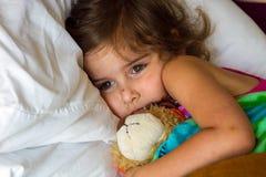 La petite fille triste a empaqueté dans le lit avec un ours bourré récemment R photos stock