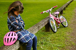 La petite fille triste ne savent pas monter un vélo Image libre de droits