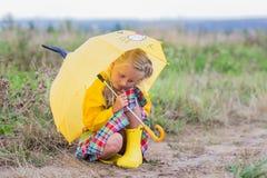 La petite fille triste se cachant de la pluie sous un parapluie photos libres de droits
