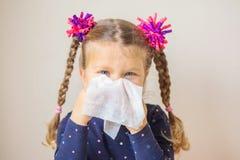 La petite fille a un écoulement nasal et souffle son nez dans un papier images libres de droits
