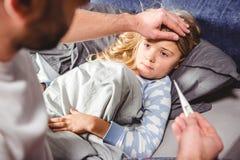 La petite fille a une fièvre et ses contrôles de père image libre de droits