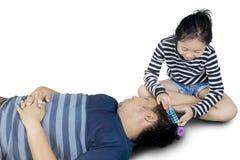 La petite fille utilise des rouleaux à son père Photographie stock libre de droits