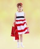 La petite fille va faire des emplettes avec les paquets rouges Images stock