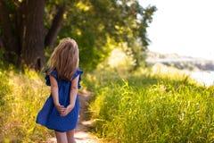 La petite fille va sur le chemin forestier d'été Images libres de droits