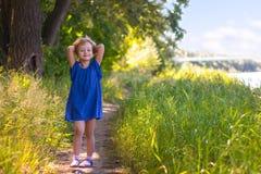 La petite fille va sur le chemin forestier d'été Photographie stock