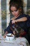 La petite fille verse le thé dans une tasse Photos stock