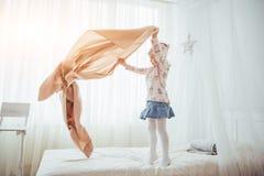 La petite fille veut s'envelopper dans une couverture dans la lumière de chambre à coucher Photo libre de droits