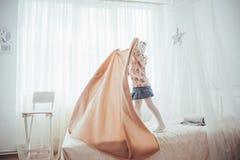La petite fille veut s'envelopper dans une couverture dans la lumière de chambre à coucher Images stock