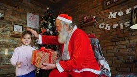 La petite fille vient chez Santa Claus, présente le cadeau de nouvelle année et étreint le grand-père de Noël banque de vidéos