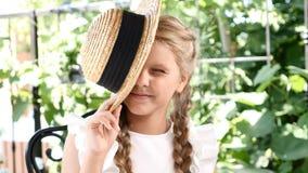La petite jolie fille ont l'amusement avec son chapeau de paille clignant de l'oeil avec son un oeil lifestyle La fille apprécien banque de vidéos