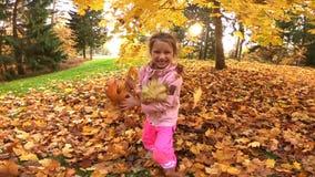 La petite jolie fille riante jette les feuilles jaunes en parc d'automne banque de vidéos