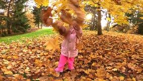 La petite jolie fille riante jette les feuilles jaunes en parc d'automne clips vidéos
