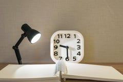 La petite lampe de plan rapproché avec la lumière avec le livre brouillé et le réveil blanc sur le bureau en bois a donné au fond Photographie stock