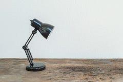 La petite lampe de plan rapproché sur le mur de bureau en bois et de ciment blanc a donné au fond une consistance rugueuse avec l Image stock