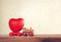La petite locomotive en bois de jouet porte le coeur, carte de jour du ` s de valentine Photographie stock