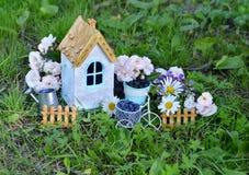 La petite maison avec les roses et la marguerite fleurit dans le jardin Image stock