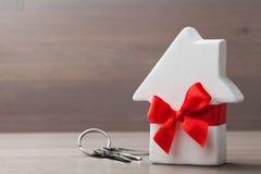 La petite maison blanche a attaché le ruban et le groupe de clés rouges sur le fond en bois Cadeau, achat d'immobiliers ou achat  Photos libres de droits