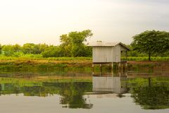 La petite maison près de la rivière a une réflexion image stock