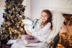 La petite princesse s'asseyent sur le fauteuil avec l'oreiller de cerfs communs par l'arbre de Noël à la maison Photographie stock libre de droits