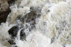 La petite rivière rugueuse fait face à des pierres Images stock