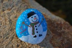 La petite roche a peint bleu-clair et blanc avec le bonhomme de neige et l'a laissé neiger Images stock