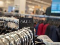 La petite section de vêtements se connectent le support accrochant en acier avec des cintres dans le magasin photographie stock