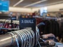la X-petite petite section supplémentaire de vêtements se connectent le support accrochant en acier avec des cintres dans le maga photographie stock libre de droits