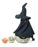 La petite sorcière s'assied sur un potiron Images stock