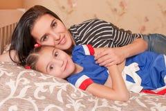 La petites fille et mère se situe dans le lit Images stock