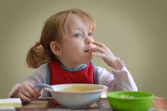 La peu de fille caucasienne blonde mignonne de cheveux bouclés assied sur la table et la consommation Elle regarde la fenêtre Images libres de droits