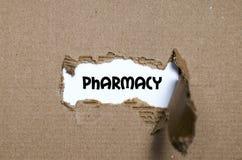 La pharmacie de mot apparaissant derrière le papier déchiré Photo stock