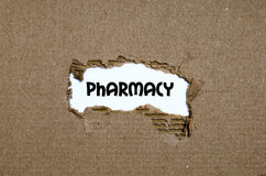 La pharmacie de mot apparaissant derrière le papier déchiré Photos libres de droits