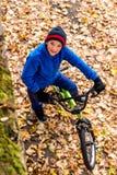 La photo aérienne d'un garçon monte une bicyclette en parc d'automne Photographie stock libre de droits