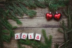 La photo avec les branches d'arbre de Noël, blocs avec les coeurs rouges du numéro 2018 et deux Photos stock